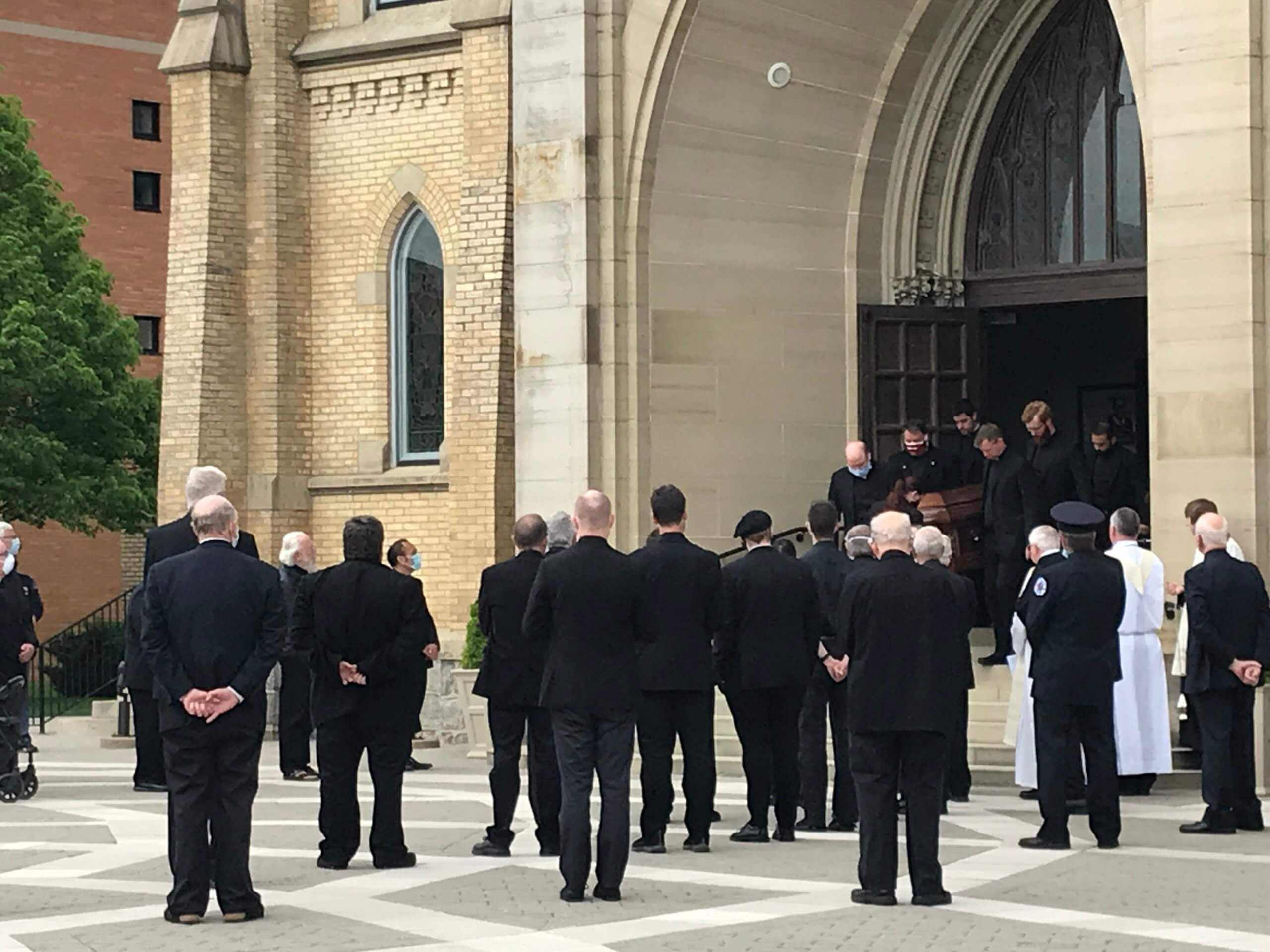 people dressed in black outside of a church